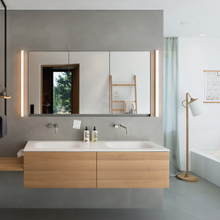 Geräumiges Nordisches Badezimmer En Suite mit grauer Wandfarbe, Betonboden, integriertem Waschbecken, grauem Boden, flächenbündigen Schrankfronten, hellen Holzschränken, weißer Waschtischplatte, Doppelwaschbecken und schwebendem Waschtisch in München