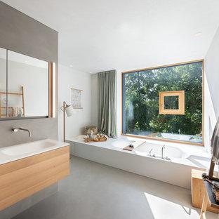 Идея дизайна: огромная главная ванная комната в скандинавском стиле с ванной в нише, зеркальной плиткой, серыми стенами, бетонным полом, монолитной раковиной, столешницей из дерева, серым полом и бежевой столешницей