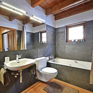 Imagen de cuarto de baño rústico, de tamaño medio, con bañera encastrada, sanitario de dos piezas, baldosas y/o azulejos grises, paredes blancas, suelo de madera en tonos medios, lavabo suspendido y suelo marrón