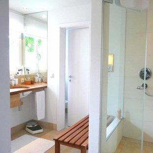 Esempio di una piccola stanza da bagno design con vasca da incasso, doccia a filo pavimento, piastrelle beige, piastrelle in travertino, lavabo integrato, top in legno e top marrone