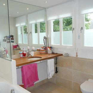 Esempio di una piccola stanza da bagno minimal con vasca da incasso, vasca/doccia, WC sospeso, piastrelle beige, piastrelle in travertino, lavabo integrato, top in legno e top marrone