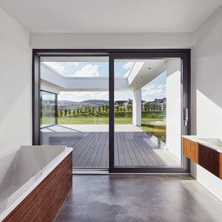 Mittelgroßes Modernes Badezimmer mit flächenbündigen Schrankfronten, dunklen Holzschränken, weißer Wandfarbe, Betonboden und integriertem Waschbecken in Düsseldorf