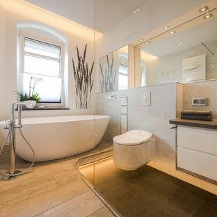 Mittelgroßes Modernes Badezimmer En Suite mit flächenbündigen Schrankfronten, weißen Schränken, freistehender Badewanne, bodengleicher Dusche, Wandtoilette mit Spülkasten, beigefarbenen Fliesen, weißer Wandfarbe, Aufsatzwaschbecken, beigem Boden und schwarzer Waschtischplatte in Dresden