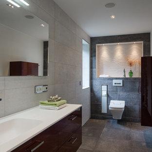 Großes Modernes Badezimmer mit flächenbündigen Schrankfronten, braunen Schränken, Wandtoilette, beigefarbenen Fliesen, Zementfliesen, weißer Wandfarbe, Zementfliesen, integriertem Waschbecken und braunem Boden in Dresden
