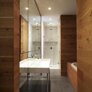 Ispirazione per una stanza da bagno padronale design di medie dimensioni con lavabo rettangolare, vasca da incasso, doccia a filo pavimento, piastrelle a specchio e pavimento in cemento