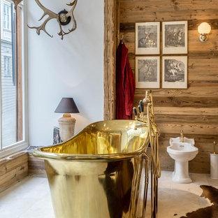 Diseño de cuarto de baño con ducha, rústico, de tamaño medio, con bañera exenta, suelo de piedra caliza, lavabo tipo consola, suelo beige, combinación de ducha y bañera, bidé y paredes marrones