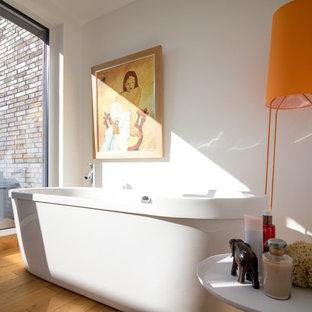 Ejemplo de cuarto de baño minimalista con bañera exenta, paredes blancas, suelo de madera clara y suelo naranja