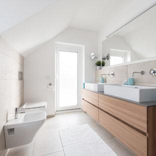 Idee per una stanza da bagno con doccia scandinava di medie dimensioni con ante lisce, ante in legno scuro, vasca da incasso, vasca/doccia, bidè, piastrelle beige, piastrelle di cemento, pareti bianche, pavimento con cementine, lavabo a bacinella e pavimento beige