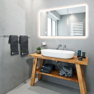 Modernes Badezimmer mit verzierten Schränken, hellbraunen Holzschränken, grauer Wandfarbe, Aufsatzwaschbecken, Waschtisch aus Holz und grauem Boden in Sonstige