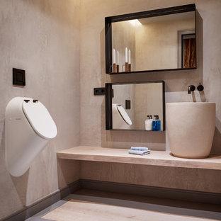 Ejemplo de cuarto de baño actual, de tamaño medio, con urinario, paredes beige, lavabo sobreencimera, suelo gris y encimeras beige