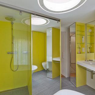 フランクフルトの中サイズのコンテンポラリースタイルのおしゃれな浴室 (壁付け型シンク、グレーのタイル、黄色い壁、磁器タイルの床、フラットパネル扉のキャビネット、黄色いキャビネット、置き型浴槽、段差なし、壁掛け式トイレ) の写真