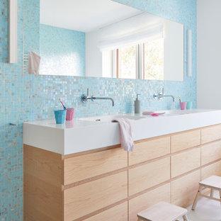 Inredning av ett modernt vit vitt badrum för barn, med släta luckor, skåp i ljust trä, blå kakel, flerfärgad kakel, mosaik, vita väggar, ett integrerad handfat och vitt golv