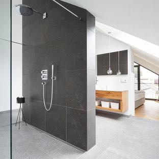 Imagen de cuarto de baño principal y abovedado, contemporáneo, con armarios abiertos, puertas de armario de madera clara, ducha a ras de suelo, baldosas y/o azulejos negros, paredes blancas, suelo gris y ducha abierta