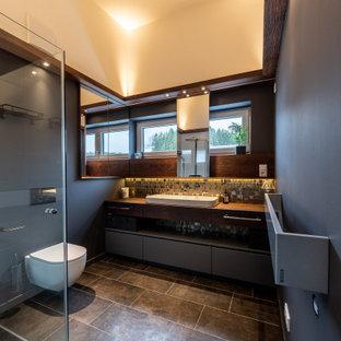 Foto di una stanza da bagno con doccia minimal di medie dimensioni con ante marroni, doccia a filo pavimento, pareti grigie, pavimento grigio e un lavabo