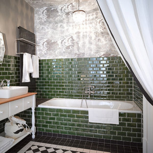 Photo of a medium sized bohemian bathroom in Berlin with a vessel sink, freestanding cabinets, white cabinets, wooden worktops, an alcove bath, a shower/bath combination, green tiles, metro tiles and grey walls.