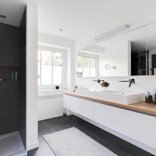 Großes Modernes Badezimmer En Suite mit weißen Schränken, bodengleicher Dusche, Aufsatzwaschbecken, offener Dusche, flächenbündigen Schrankfronten, weißer Wandfarbe, Waschtisch aus Holz, schwarzem Boden und brauner Waschtischplatte in Düsseldorf