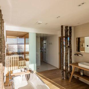 Mittelgroßes Asiatisches Badezimmer mit freistehender Badewanne, Steinfliesen, beiger Wandfarbe, gebeiztem Holzboden, Aufsatzwaschbecken, Waschtisch aus Holz und brauner Waschtischplatte in Sonstige