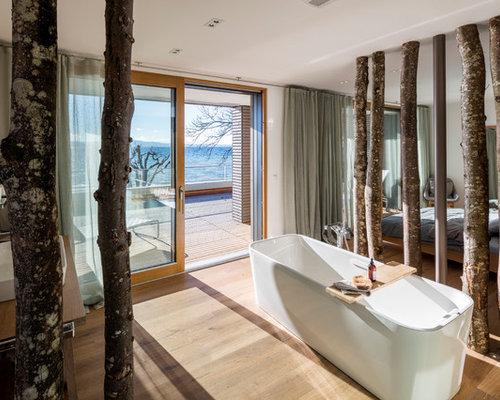 Mittelgroßes Modernes Badezimmer En Suite Mit Freistehender Badewanne,  Weißer Wandfarbe, Hellem Holzboden Und Aufsatzwaschbecken