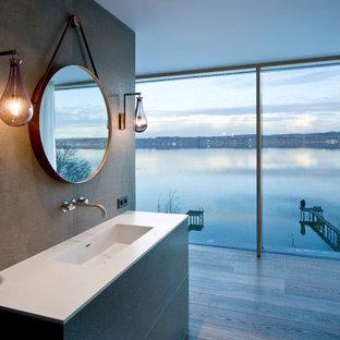 Imagen de cuarto de baño actual con baldosas y/o azulejos grises, losas de piedra, paredes grises, suelo de madera en tonos medios, lavabo integrado y encimera de acrílico