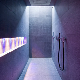 Inredning av ett modernt stort badrum, med en dubbeldusch, grå kakel, stenhäll och grå väggar