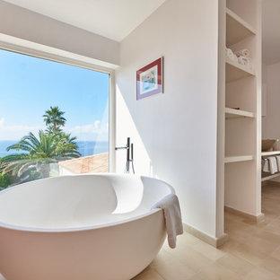 Diseño de cuarto de baño marinero con armarios abiertos, bañera exenta, paredes blancas, suelo de baldosas de cerámica, lavabo sobreencimera y suelo beige