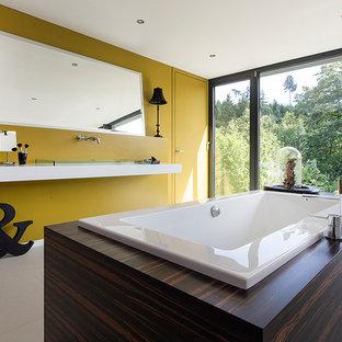 Ispirazione per una stanza da bagno design di medie dimensioni con vasca da incasso, pareti gialle, lavabo da incasso e top in vetro