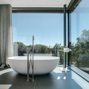 Modernes Badezimmer mit freistehender Badewanne und grauem Boden in München