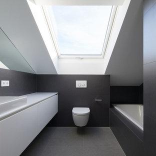 Kleines Modernes Badezimmer Mit Flächenbündigen Schrankfronten, Weißen  Schränken, Wandtoilette, Grauen Fliesen, Schwarzen