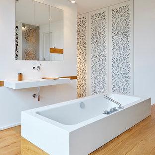 Mittelgroßes Modernes Badezimmer En Suite mit freistehender Badewanne, weißer Wandfarbe, Wandwaschbecken, braunem Boden, flächenbündigen Schrankfronten, weißen Schränken, braunem Holzboden, Mineralwerkstoff-Waschtisch, bodengleicher Dusche, Wandtoilette und Schiebetür-Duschabtrennung in Köln