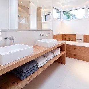 Foto di una grande stanza da bagno moderna con nessun'anta, ante in legno scuro, vasca ad alcova, piastrelle bianche, pareti bianche, lavabo a bacinella, top in legno e top marrone
