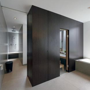 Immagine di una sauna moderna di medie dimensioni con ante lisce, ante in legno bruno, vasca da incasso, doccia a filo pavimento, WC sospeso, piastrelle grigie, piastrelle in ceramica, pareti grigie, pavimento con piastrelle in ceramica, pavimento grigio e doccia aperta