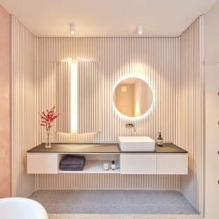 Großes Modernes Duschbad mit Lamellenschränken, weißen Schränken, freistehender Badewanne, bodengleicher Dusche, Wandtoilette, rosa Wandfarbe, Terrazzo-Boden, Aufsatzwaschbecken, Waschtisch aus Holz, grauem Boden, offener Dusche und schwarzer Waschtischplatte in München