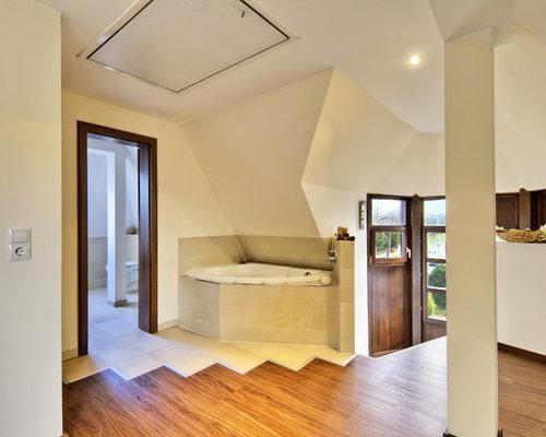 Großes Modernes Badezimmer Mit Eckbadewanne, Weißer Wandfarbe Und Braunem  Holzboden In Sonstige