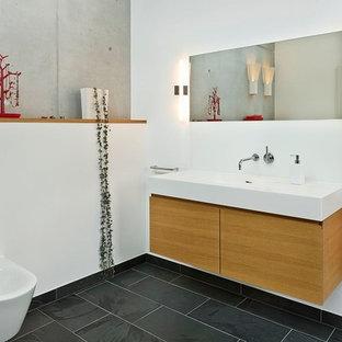 Diseño de cuarto de baño actual, de tamaño medio, con armarios con paneles lisos, puertas de armario de madera oscura, paredes blancas, suelo de pizarra, lavabo integrado y bidé