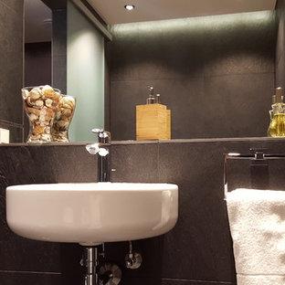 Immagine di una grande sauna contemporanea con consolle stile comò, ante nere, vasca idromassaggio, doccia aperta, piastrelle nere, piastrelle in pietra, lavabo sospeso, top piastrellato, pavimento in gres porcellanato, WC a due pezzi, pareti nere, pavimento nero, doccia aperta e top nero
