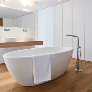 Großes Modernes Badezimmer En Suite mit flächenbündigen Schrankfronten, weißen Schränken, freistehender Badewanne, Waschtisch aus Holz, weißer Wandfarbe, hellem Holzboden, braunem Boden und Waschtischkonsole in Stuttgart