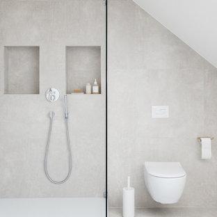 Modernes Duschbad mit Wandtoilette, grauen Fliesen, weißer Wandfarbe und grauem Boden in Frankfurt am Main