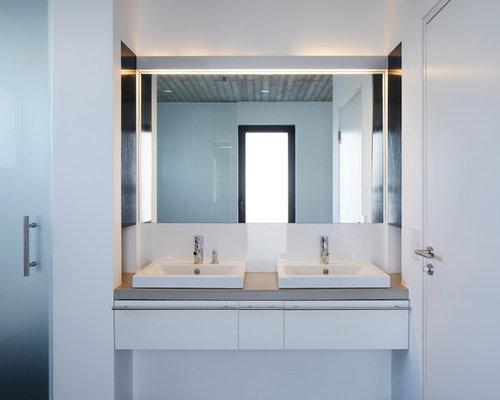 Modernes Badezimmer Mit Flächenbündigen Schrankfronten, Weißen Schränken,  Weißer Wandfarbe, Aufsatzwaschbecken, Weißen Fliesen