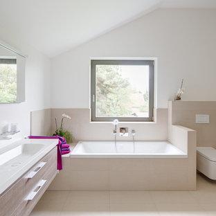 Modelo de cuarto de baño principal, actual, grande, con armarios con paneles lisos, puertas de armario de madera oscura, sanitario de pared, baldosas y/o azulejos beige, paredes blancas, bañera empotrada y lavabo integrado