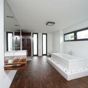 Großes Modernes Duschbad mit braunem Holzboden, flächenbündigen Schrankfronten, hellbraunen Holzschränken, freistehender Badewanne, offener Dusche, Wandtoilette, weißer Wandfarbe, Aufsatzwaschbecken, Waschtisch aus Holz, braunem Boden und Falttür-Duschabtrennung in Stuttgart