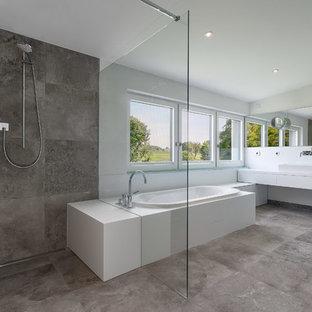 Idee per un'ampia stanza da bagno padronale minimal con lavabo a bacinella, ante lisce, ante bianche, vasca da incasso, doccia a filo pavimento, piastrelle grigie, lastra di pietra e pareti bianche
