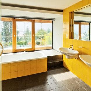 Immagine di una grande stanza da bagno minimal con lavabo sospeso, vasca da incasso, piastrelle gialle e pareti bianche