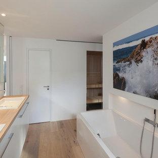 Modelo de cuarto de baño contemporáneo, grande, con bañera encastrada, paredes blancas, suelo de madera en tonos medios, lavabo encastrado y encimera de madera