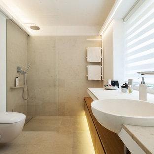 Пример оригинального дизайна: маленькая ванная комната в современном стиле с плоскими фасадами, светлыми деревянными фасадами, инсталляцией, серой плиткой, белыми стенами, накладной раковиной, душевой кабиной, полом из известняка, столешницей из известняка, душем в нише и плиткой из известняка