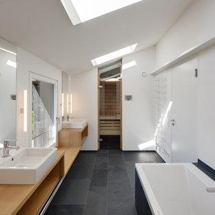 Cette photo montre une grand salle de bain principale scandinave avec une vasque, un plan de toilette en bois, une baignoire posée, un mur blanc, un sol en ardoise, un placard sans porte, des portes de placard en bois clair, un carrelage noir et un plan de toilette marron.