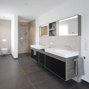 Großes Modernes Duschbad mit flächenbündigen Schrankfronten, schwarzen Schränken, offener Dusche, Wandtoilette mit Spülkasten, beigefarbenen Fliesen, Zementfliesen, weißer Wandfarbe, Zementfliesen, Aufsatzwaschbecken, Waschtisch aus Holz, schwarzem Boden, offener Dusche und grauer Waschtischplatte in München