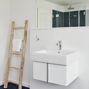 Kleines Modernes Badezimmer En Suite mit flächenbündigen Schrankfronten, weißen Schränken, weißer Wandfarbe, Aufsatzwaschbecken, weißen Fliesen und Mineralwerkstoff-Waschtisch in Sonstige