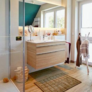 Mittelgroßes Maritimes Duschbad mit flächenbündigen Schrankfronten, weißer Wandfarbe, hellen Holzschränken, integriertem Waschbecken, beigem Boden, weißer Waschtischplatte, Duschnische, weißen Fliesen, braunem Holzboden und Falttür-Duschabtrennung in Sonstige