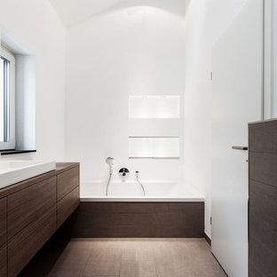 Geräumiges Modernes Duschbad mit flächenbündigen Schrankfronten, dunklen Holzschränken, Einbaubadewanne, braunen Fliesen, weißer Wandfarbe, Waschtisch aus Holz, Porzellan-Bodenfliesen und Aufsatzwaschbecken in Dortmund