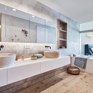 Foto de cuarto de baño principal, actual, grande, con armarios con paneles lisos, puertas de armario blancas, baldosas y/o azulejos grises, paredes grises, suelo de madera en tonos medios, lavabo sobreencimera, suelo marrón, encimeras blancas y bañera encastrada